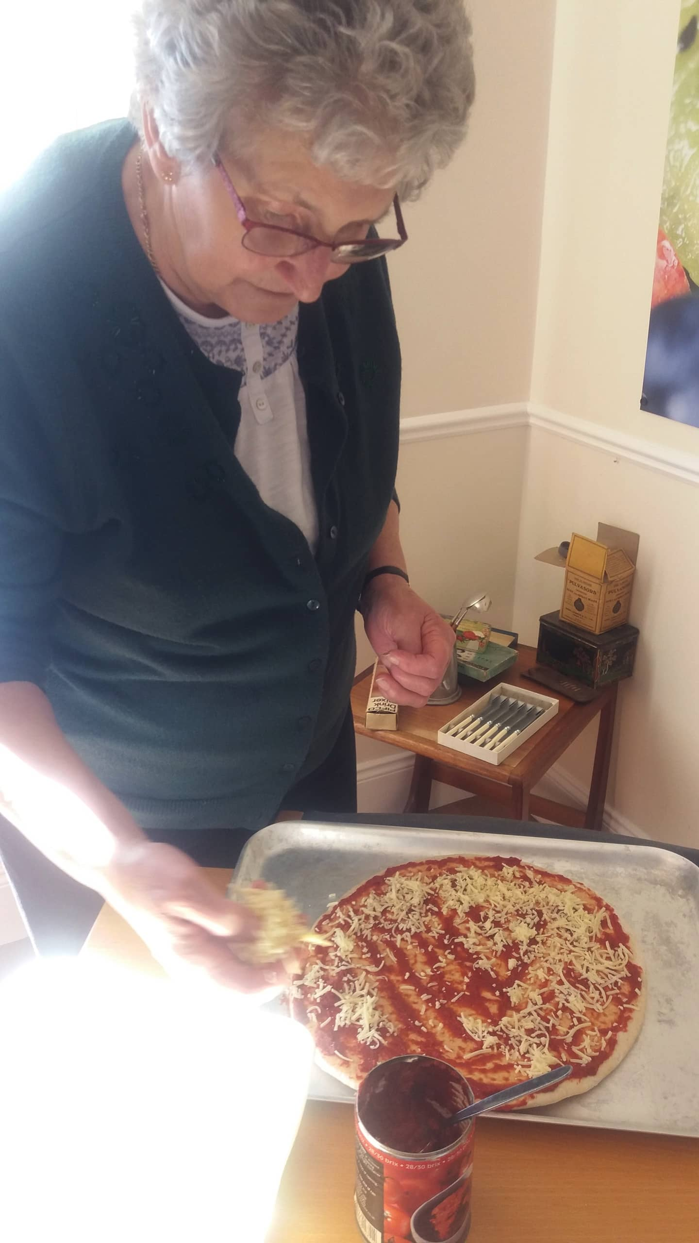 Resident carefully creating her pizza.