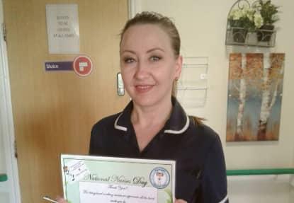 Nurse Saly Joseph holding her nurse stars award certificate