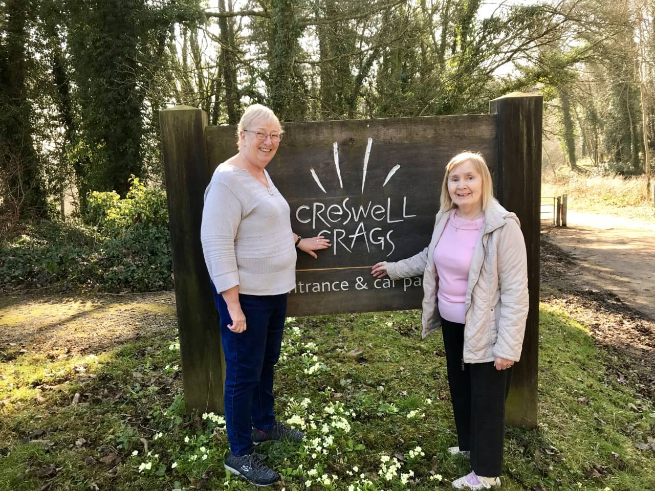 Residents outside Creswell Crags sign.