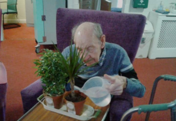 Resident watering his new house plant.
