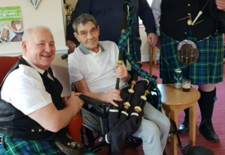 Resident posing for a picture with a set of Bagpipes