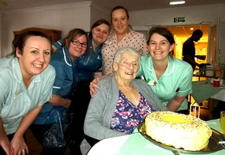 Mary enjoying her cake with staff on her 90th birthday.