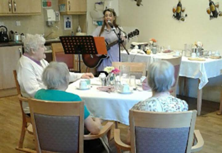 Tracey Lee playing guitar for residents at Lofthouse Grange & Lodge Care Home