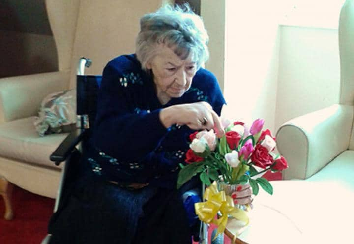 Resident enjoying arranging flowers.