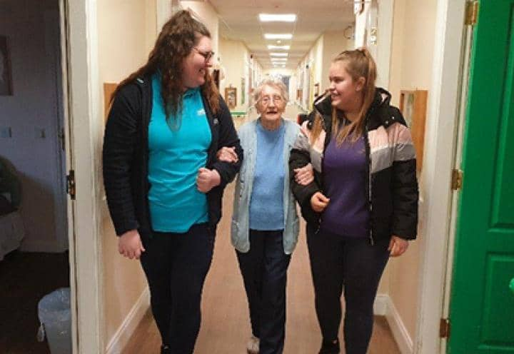 Residents walking with the homes Activity Coordinator and a visitor from the Girls Brigade.