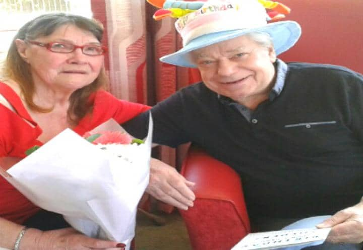 Resident Bryan and his wife holding gifts
