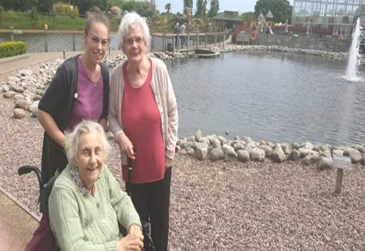 Residents and staff pose by the pond