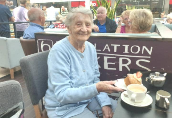 Resident enjoying a cup of tea and some sweet treats