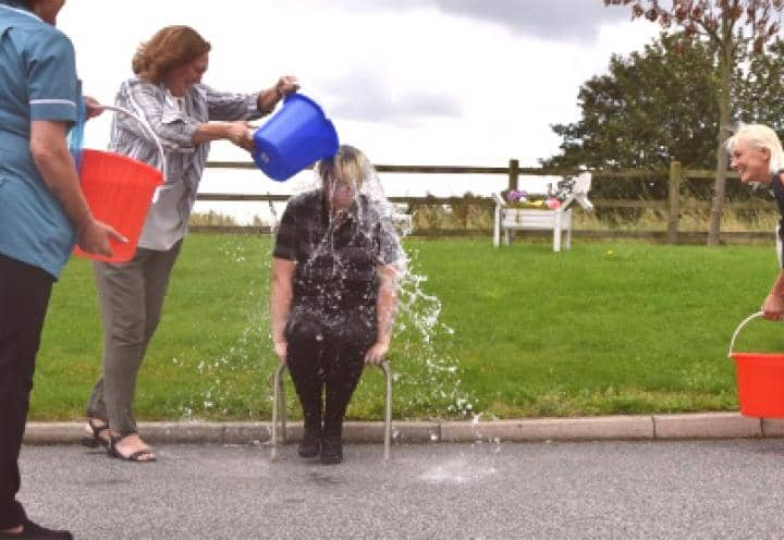 Sarah the homes deputy manager getting water thrown over her