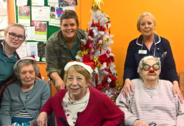residents sitting infront of their decorated Christmas Tree