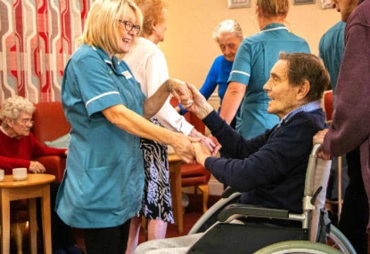 staff dancing with resident in a wheelchair