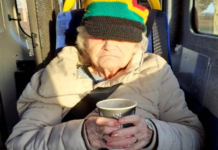 resident having a hot drink on the bus.