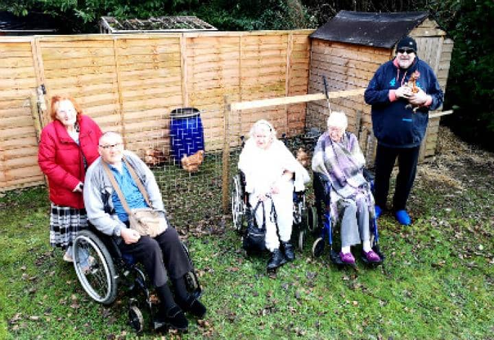 residents stood outside their new shed.